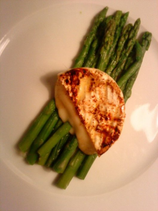 Cooked goat cheese on steamed asparagus.